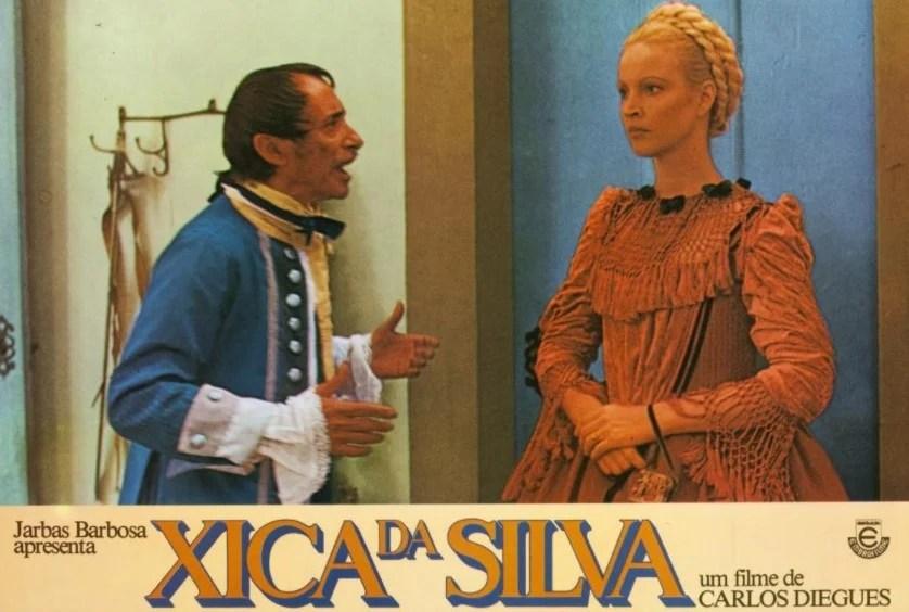 """Cartaz com a cena do filme """"Xica da Silva"""", onde aparece Elke vestida com um traje de época vermelho e cabelo longo preso com tranças no topo de cabeça."""