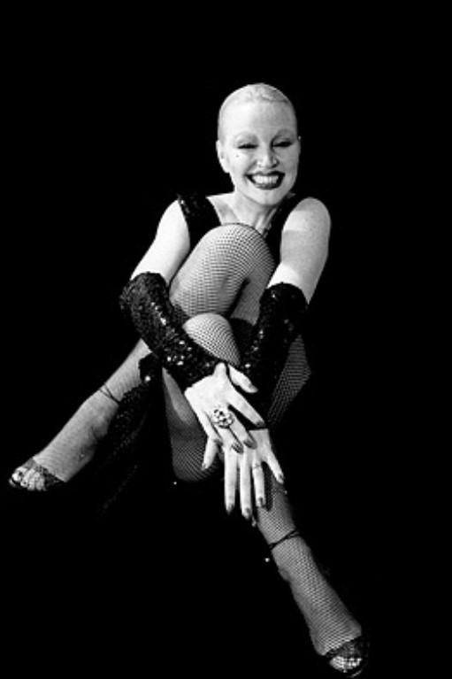 Foto em preto e branco de Elke maravilha posando como modelo sentada no chão, com um fundo todo preto e pernas cruzadas.