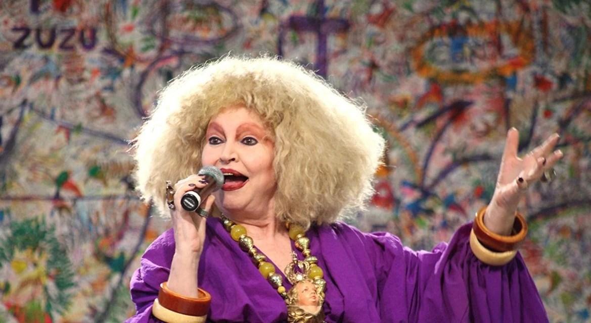Foto de Elke Maravilha mais velha falando em um microfone com um vestido de mangas longas roxo e cabelo loiro curto e muito armado.