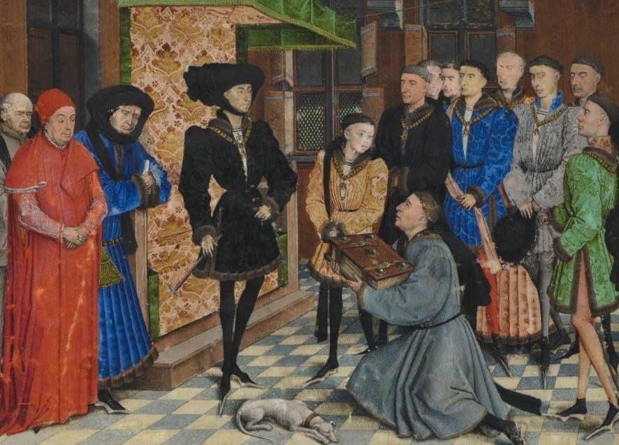 """Pintura na qual aparece Filipe """"o bom"""", duque de Borgonha, posando no centro com um traje preto com botões e um chapéu e rodeado de pessoas, com alguém a lhe oferecer um livro"""
