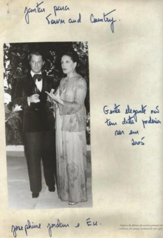 Imagem em preto e branco de Guilherme Guimarães nos anos 80 posando em pé vestido de smoking preto e gravata borboleta preta em um jantar para a Town & Country ao lado de Josephine Jordan