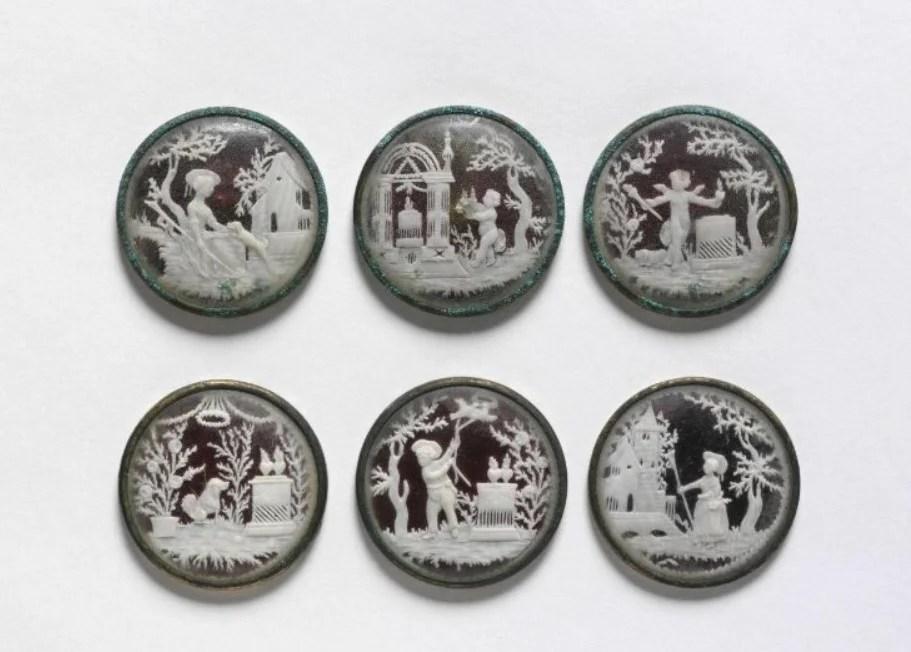 Conjunto de seis botões feito em marfim talhado com vidro e metal com cenas de pastores e pastagens