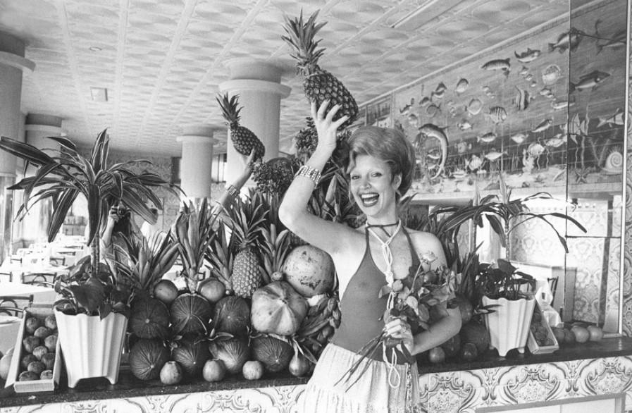 Foto em preto e branco de Elke Maravilha posando com um vestido decotado e segurando um abacaxi na cabeça diante de um espelho rodeado de frutas e plantas.