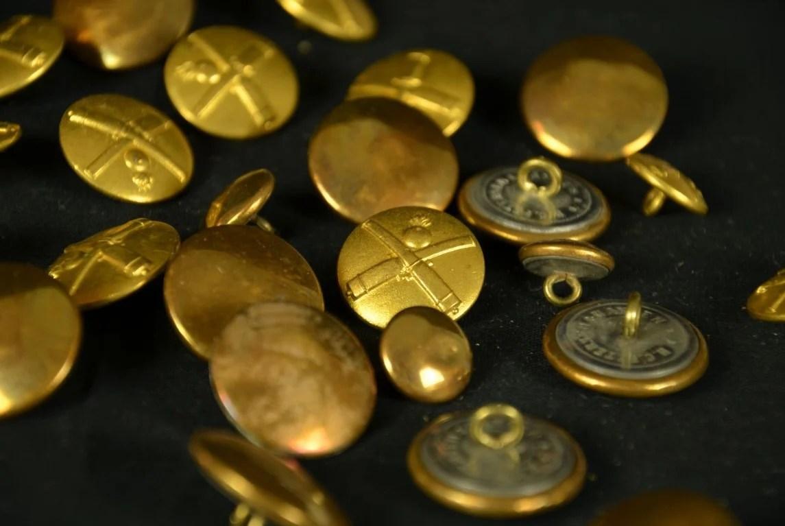 Imagem de vários botões de bronze decorado com um desenho em relevo de armas cruzadas sobre fundo preto