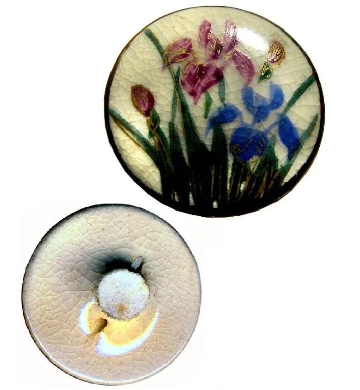 Foto de um botão de roupa feito de porcelana japonesa branca decorado com flores vermelhas e azuis