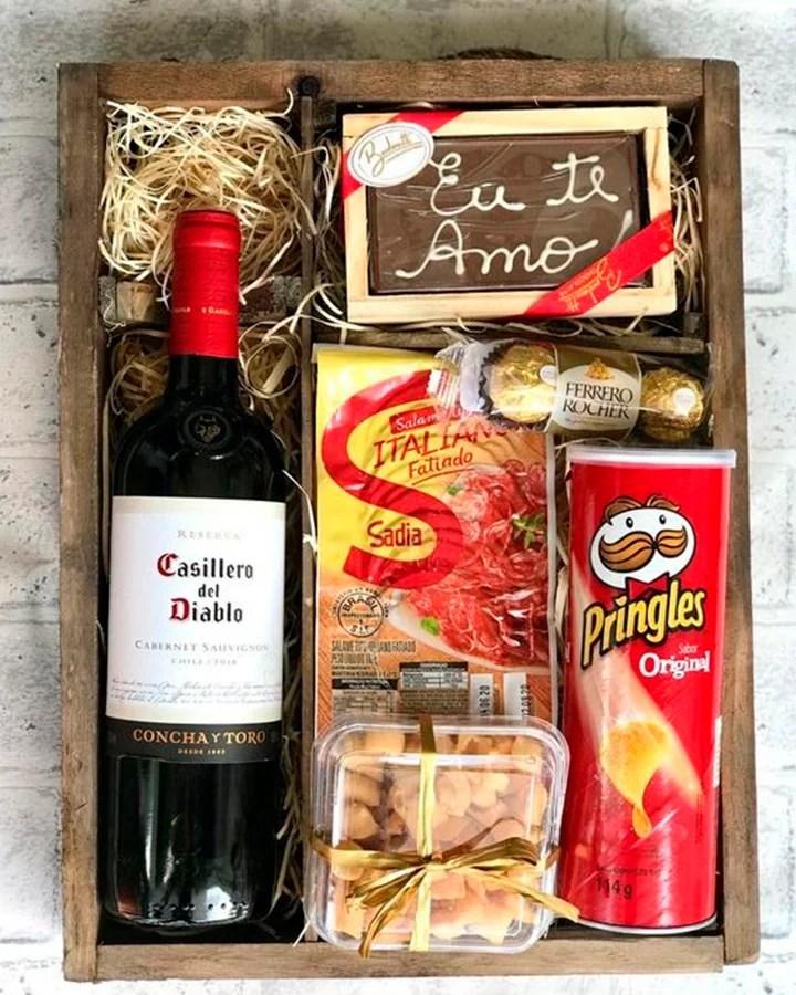 Cesta feita em uma caixa, com vinho, Pringles, e outros petiscos