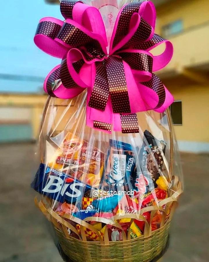 Cesta com vários doces dentro, decorada com um laço rosa