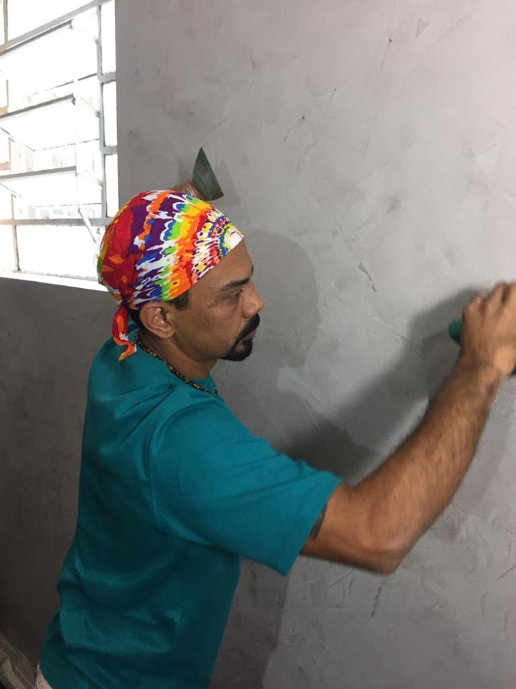 Homem pintando a parede.