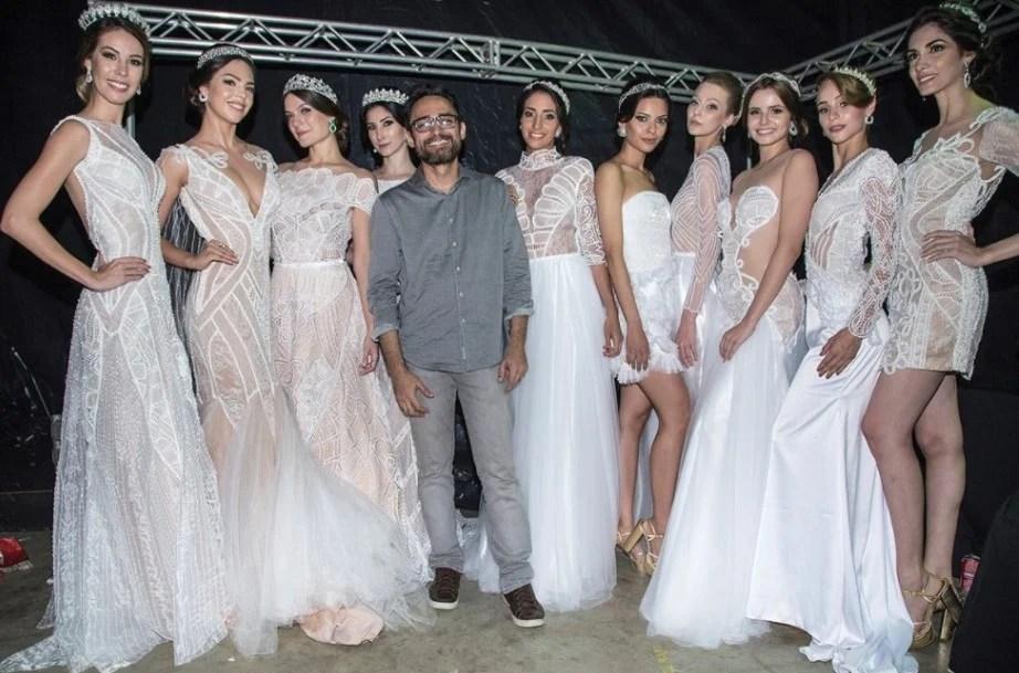 O estilista Ivanildo Nunes no centro da foto posando rodeado de modelos trajando vestidos de noiva brancos feitos com rendas e outras técnicas