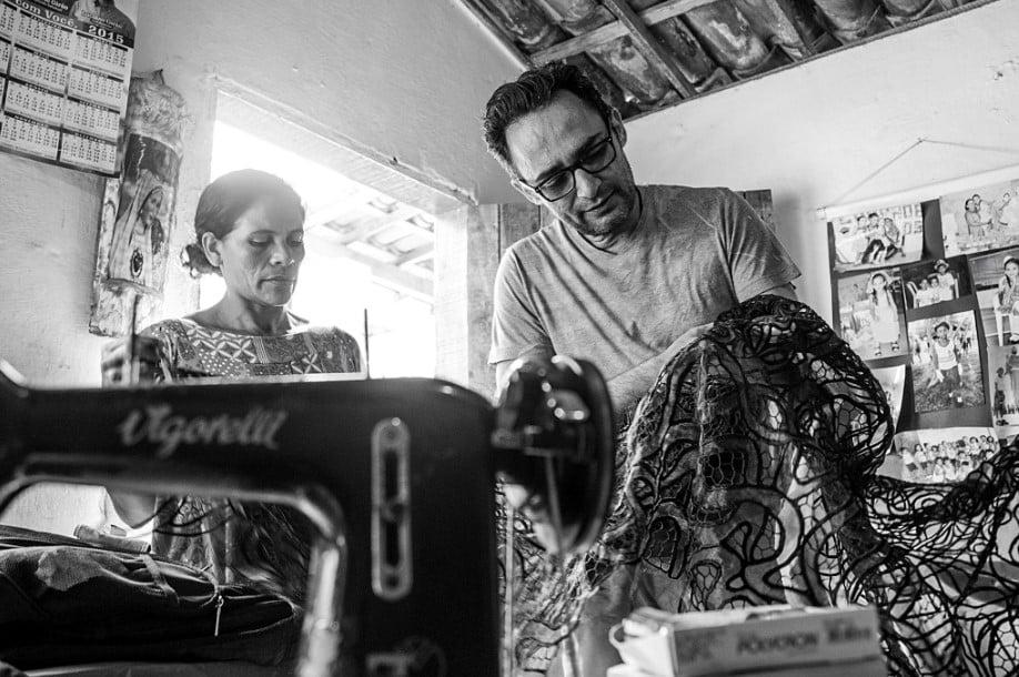 Foto em preto e branco do estilista Ivanildo Nunes a segurar nas mãos uma renda preta ao lado de uma artesã e uma máquina de costura