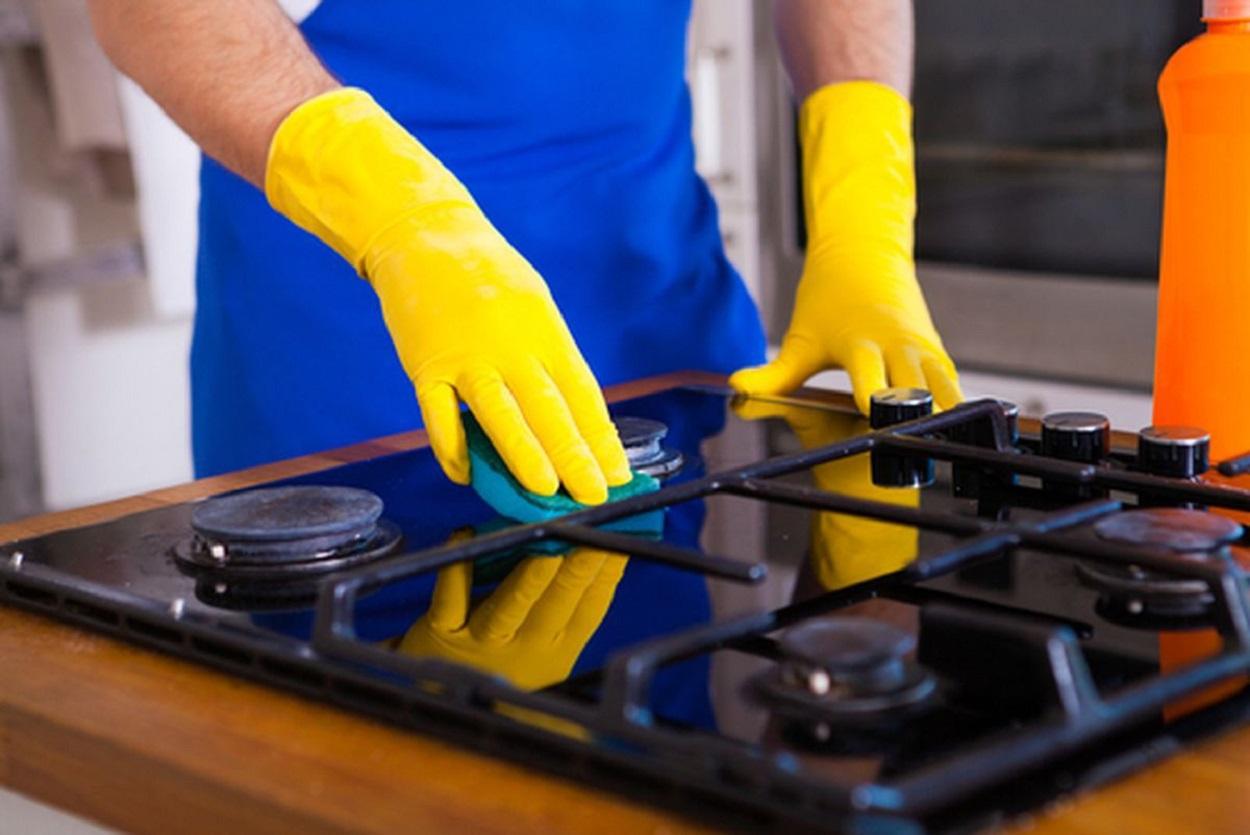 Homem fazendo a limpeza de fogão.