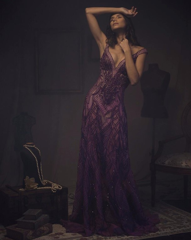 Modelo posando em pé com um vestido de festa de renda roxo de Ivanildo Nunes em um fundo escuro com