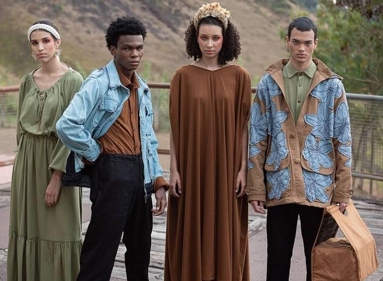 Quatro modelos posando lado a lado ao ar livre com peças da coleção Conspiração de Ronaldo Silvestre, com jaquetas jeans e vestidos soltos e longos em verde e marrom