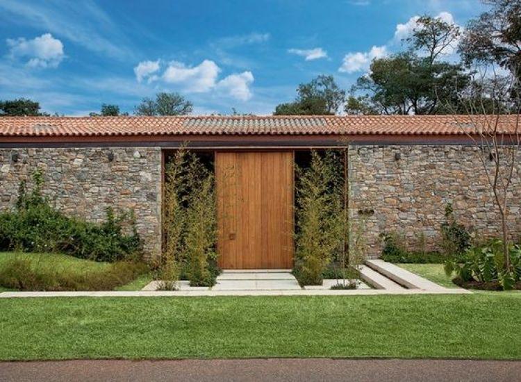 Fachada com muro de pedra e porta de madeira.