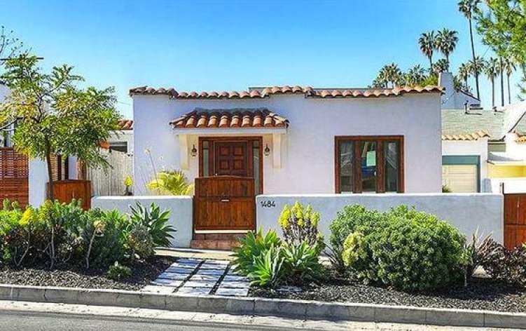Casa branca com portão pequeno de madeira.