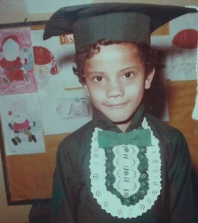Foto colorida de Ronaldo Silvestre criança vestido com um chapéu e roupa de formatura verde diante de um quadro com desenhos pendurados.