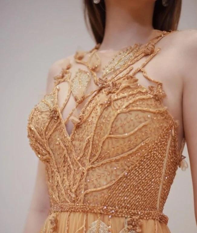 Foto da parte superior de uma modelo posando com um vestido dourado de Ivanildo Nunes