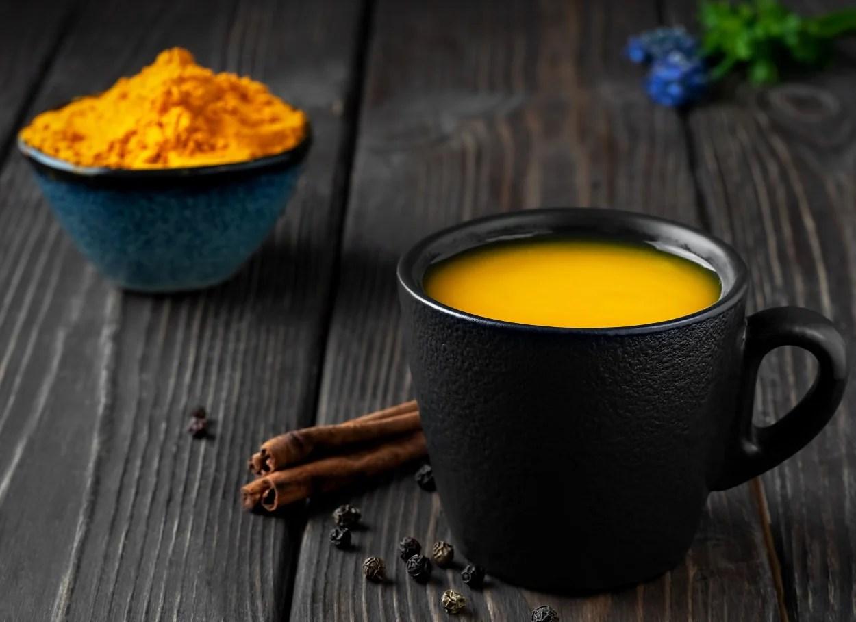 Foto de caneca preta com chá de açafrão ao lado de pimenta-do-reino e canela