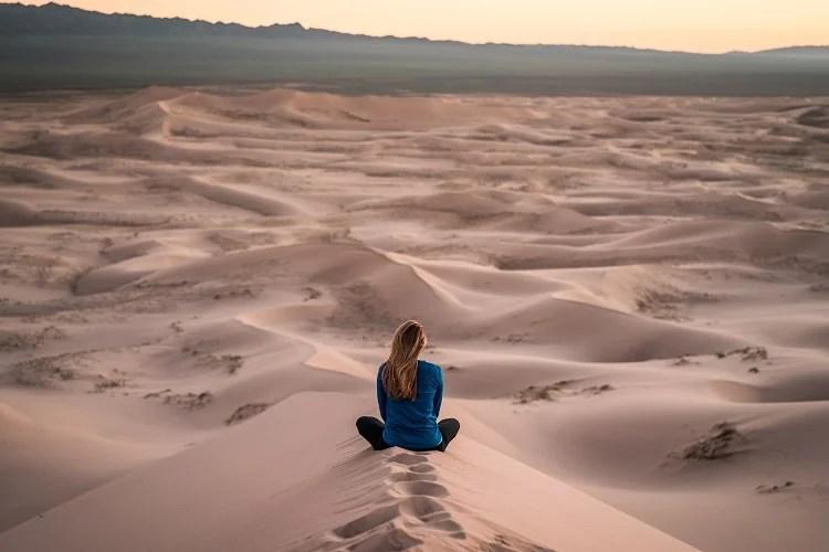 foto de mulher de costas sentada em dunas do deserto