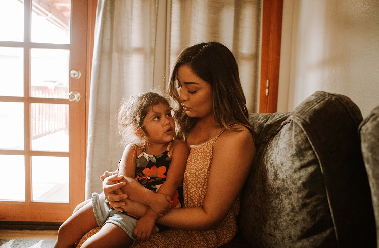 Foto de mulher sentada com a sobrinha no colo