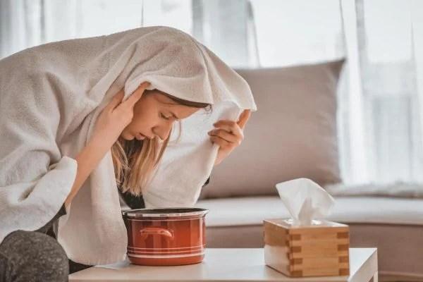 Mulher inalando vapor de eucalipto com toalha na cabeça
