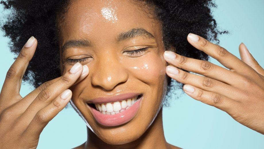 Mulher aplicando o Cleansing Oil e sorrindo