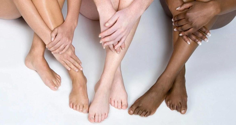Pernas cruzadas de três mulheres demonstrando depilação