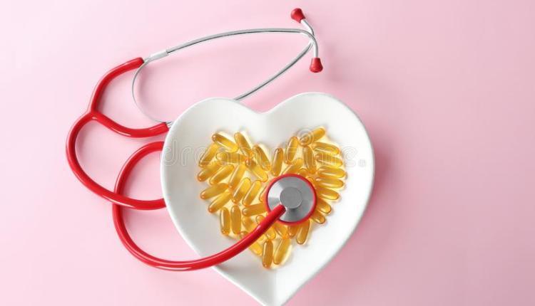Vasilha em formato de coração com capsulas de óleo de alho e estetoscópio