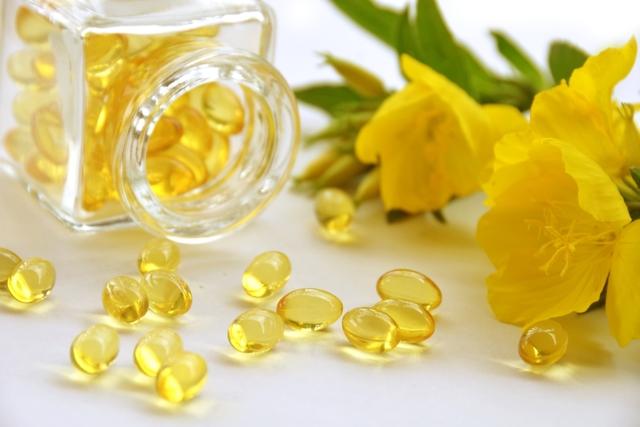 Frasco de vidro com capsulas de óleo de prímula ao lado da planta de origem do óleo