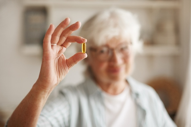 Mulher idosa segurando uma capsula de óleo de prímula