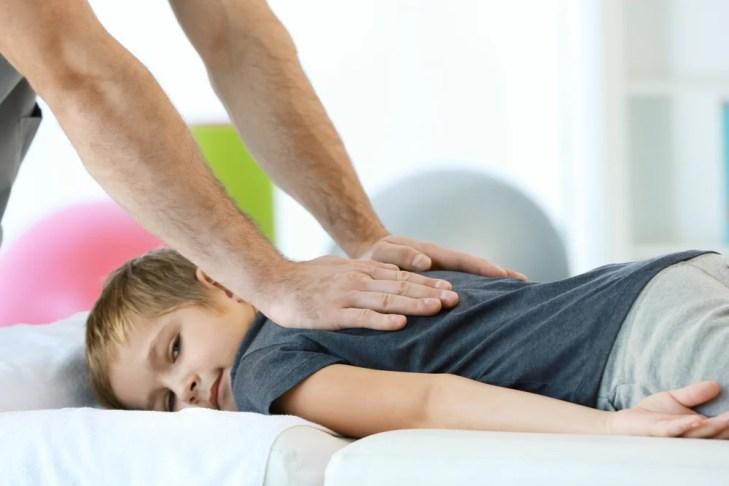 Quiroprata realizando procedimento em jovem