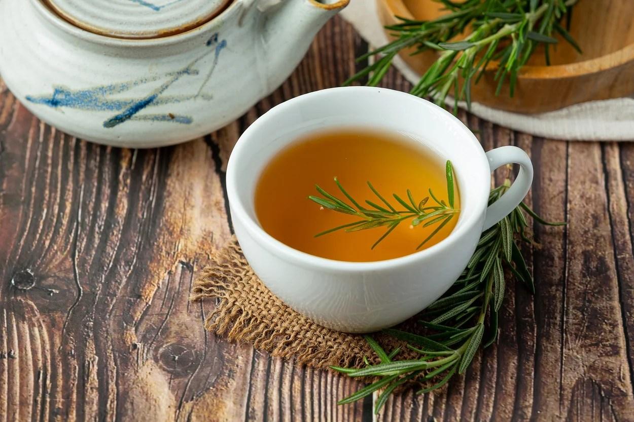 Foto de xícara de porcelana com chá de alecrim sobre mesa de madeira