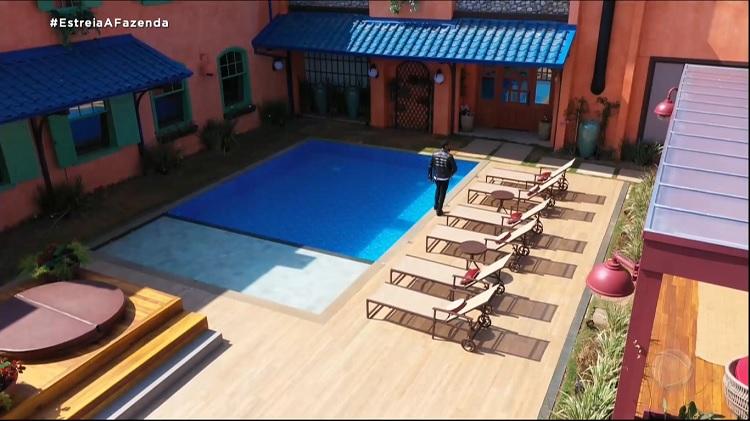 Foto de Nego do Borel andando ao lado da piscina