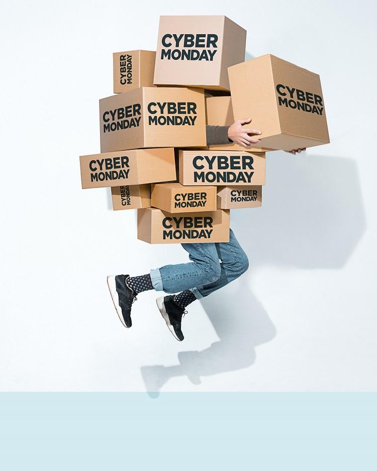 """Foto de pessoa segurando caixas de papelão onde se lê """"Cyber Monday"""""""