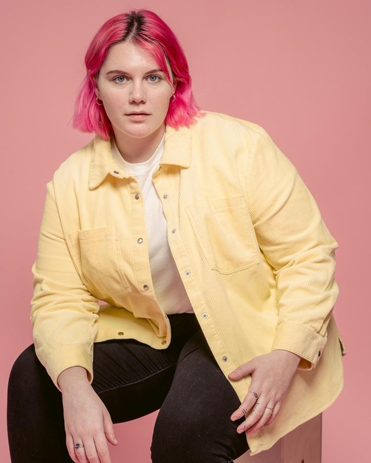 Foto de mulher com camisa amarela.