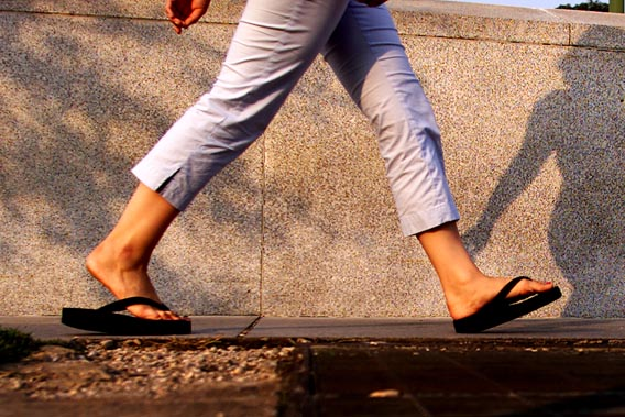 A woman walks with flip flops in Washington, July 15, 2003. Flip-flops in the nation's capital typically mean politicians switching positions on an important issue like abortion or taxes, but not this summer. Instead, the flip-flop resonating in Washington and across the country is the snapping sound coming from women's feet as they adopt thong sandals as the comfortable shoes to wear to work, on a hot date or just to the grocery store. Picture taken July 15, 2003. NO RIGHTS CLEARANCES OR PERMISSIONS ARE REQUIRED FOR THIS IMAGE REUTERS/William Philpott/FEATURE-LIFE-FLIPFLOPS WP/HB - RTRTFB