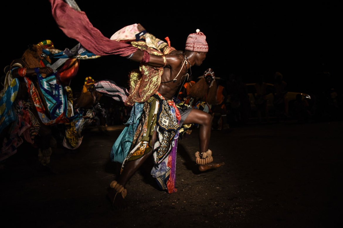 A group in vividly coloured costumes performs a dance from the Bijagos ethnic group in Bissau, as they compete in carnival. [Ricci Shryock/Al Jazeera]