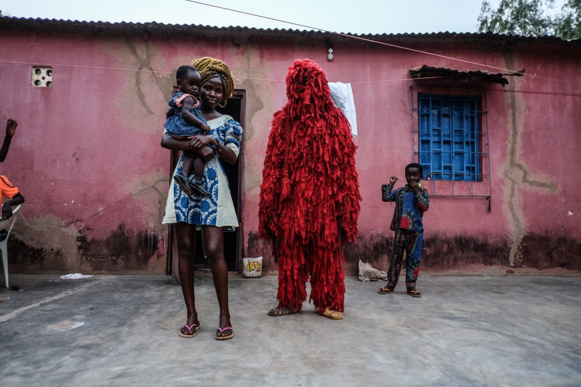 A man dressed as Kankouran, the traditional Mandinka creature that chases away evil spirits after circumcision ceremonies in Mandinka tradition, is pictured with his family in Bissau. [Ricci Shryock/Al Jazeera]