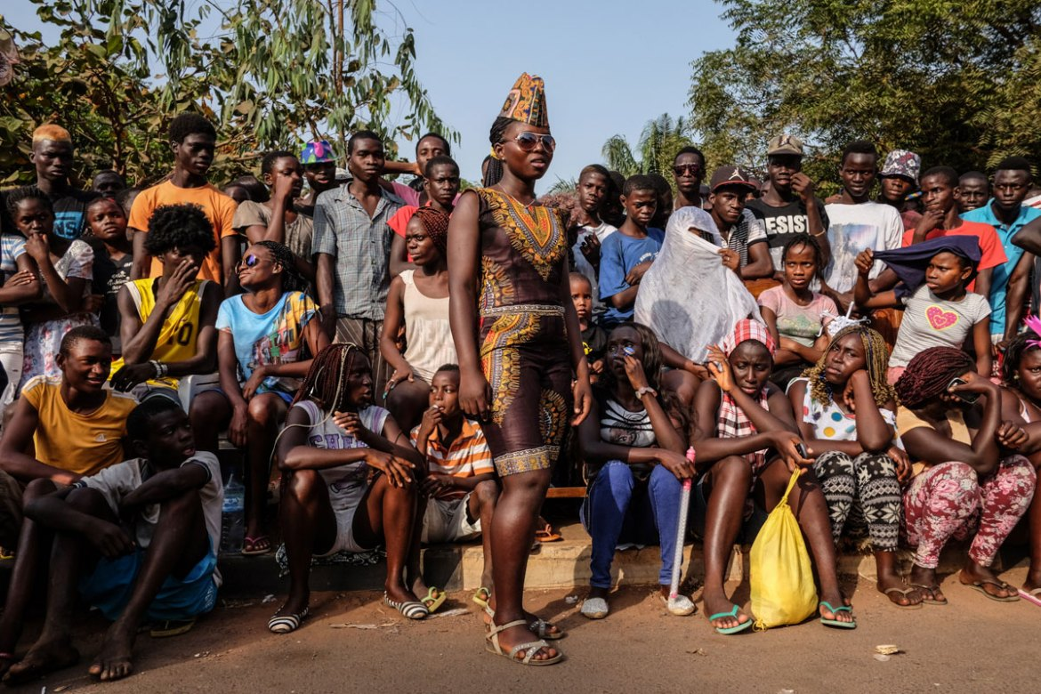 Spectators line up to watch the first day of carnival competition which features traditional dances and songs from different parts of Guinea Bissau. [Ricci Shryock/Al Jazeera]