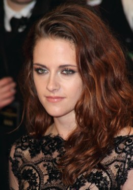 A brunette Kristen Stewart with romantic waves and highlights