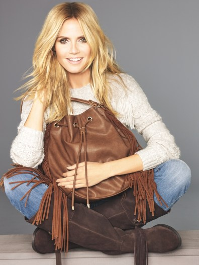 Heidi poses with a fringe bag and jeans in this image