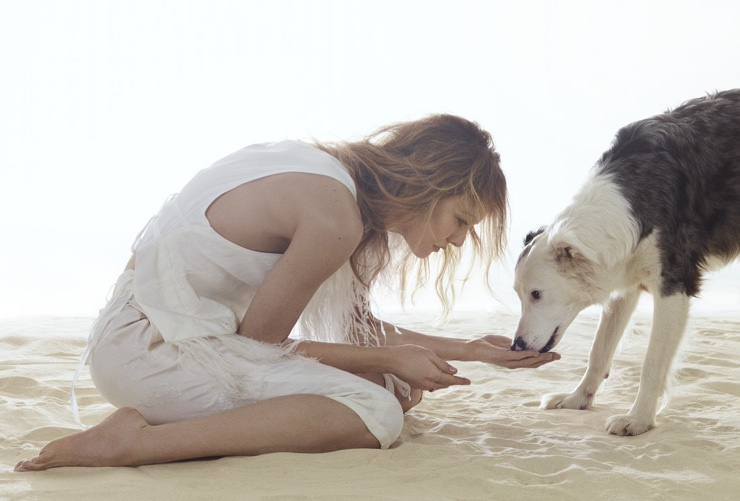 Dressed in white, Vanessa Paradis poses with a dog in this shot