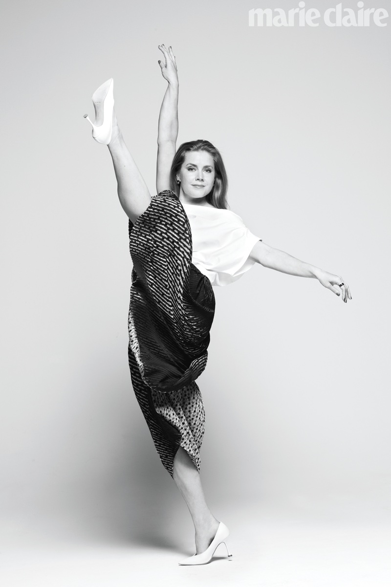 Kicking up her heels, Amy Adams poses in Issey Miyake top and pants with Manolo Blahnik shoes