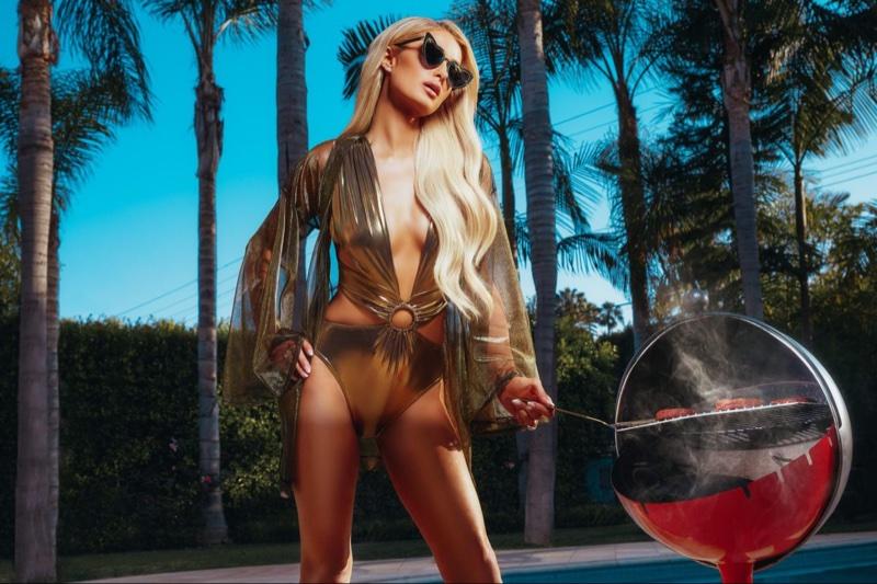 Wearing a gold swimsuit, Paris Hilton models Boohoo collaboration