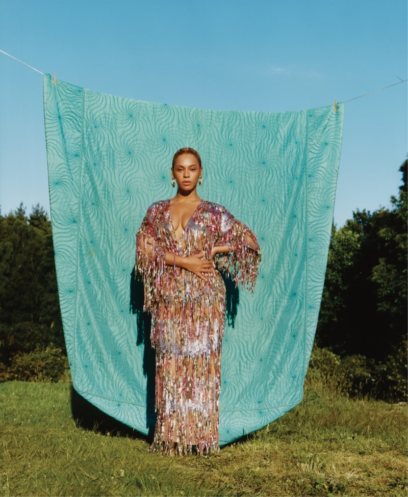 Posing outdoors, Beyonce wears Gucci dress and Bulgari earrings