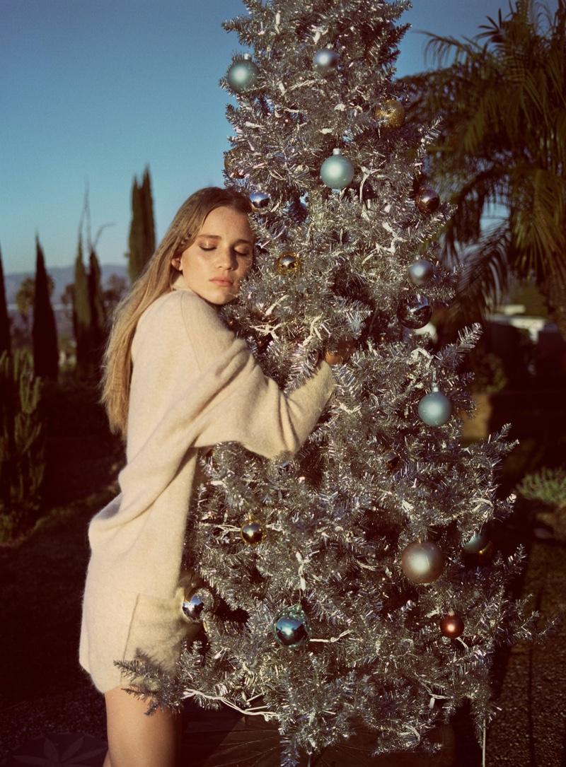 Posing with a Christmas tree, Rebecca Leigh Longendyke wears Zara sweater.