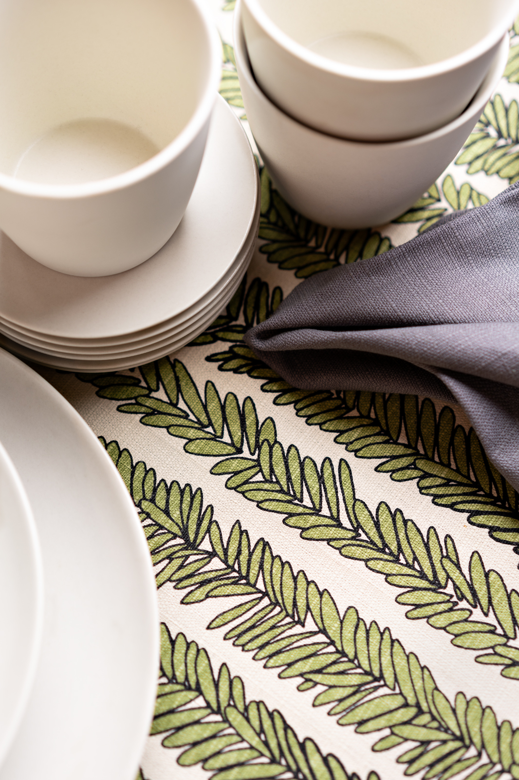 a table cloth with some cups and plates