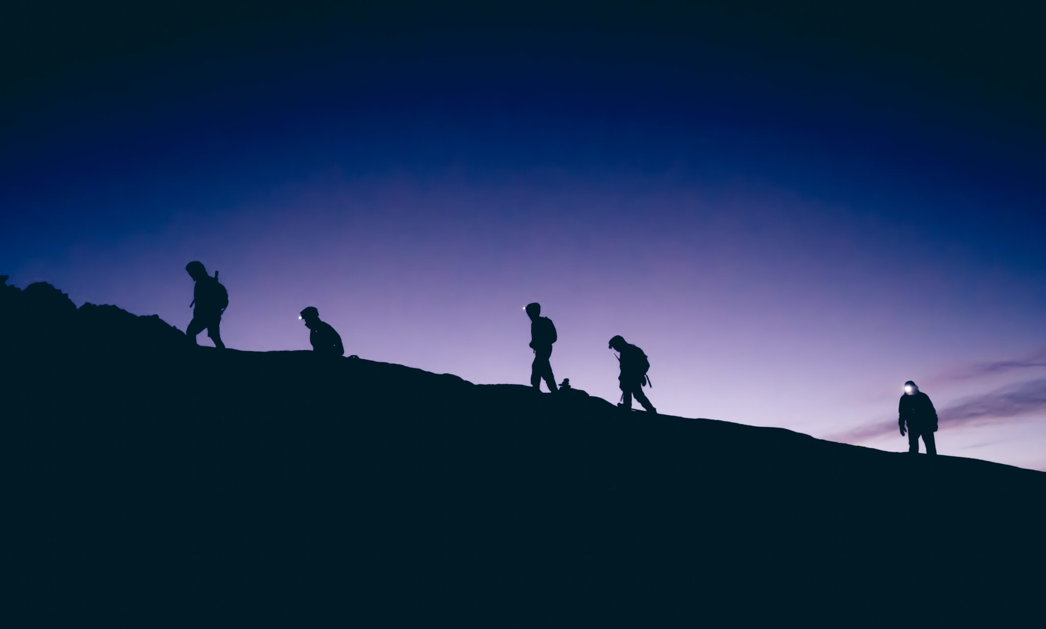 Five people are walking on a mountain in sunset.