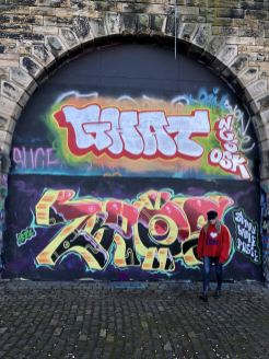 An image of pixie Tenenbaum walking in front of a graffiti wall wearing an oversized red sweater and blue denim jeans. Fashion Voyeur Blog