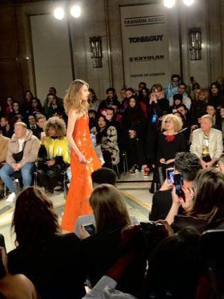 Malan Breton FW18 Fashion Scout London Fashion Week a model wearing an orange leather gown on the runway
